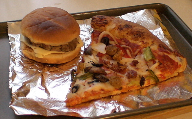 Photograph of a slice of pizza and a cheeseburger.